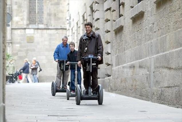 Unos turistas se desplazan en segway por el centro de Barcelona.