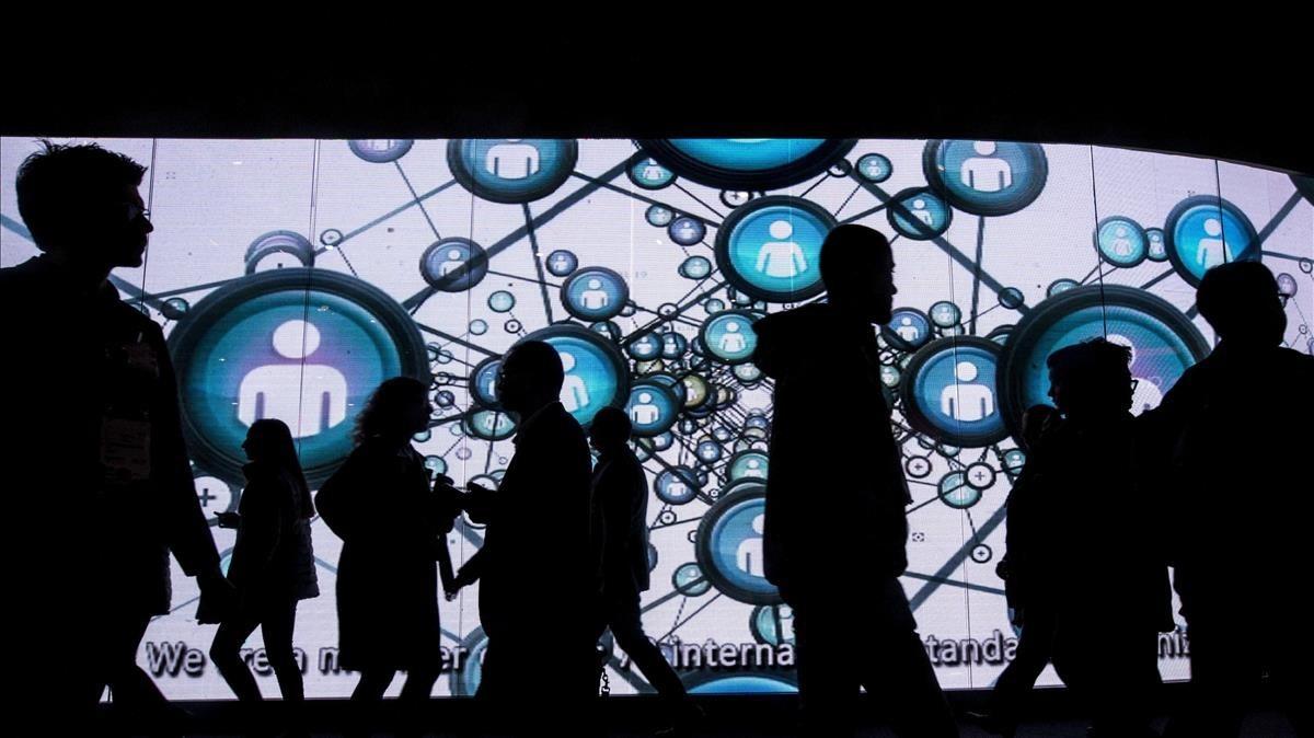 Visitantes del Mobile World Congress ante una enorme pantalla.