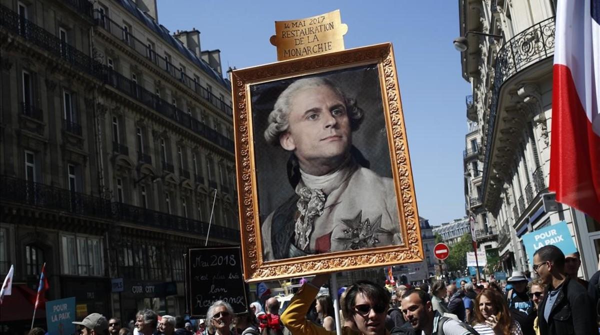 Los manifestantes contrarios a Macron muestran un retrato del rey Luis XIV con la cara del actual presidente.