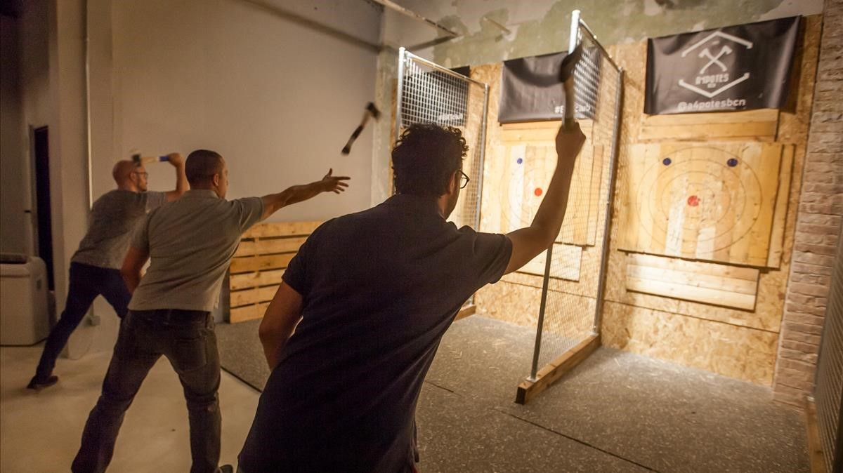 Tres chicos tiran hachas en Barcelona Axe Throwing.