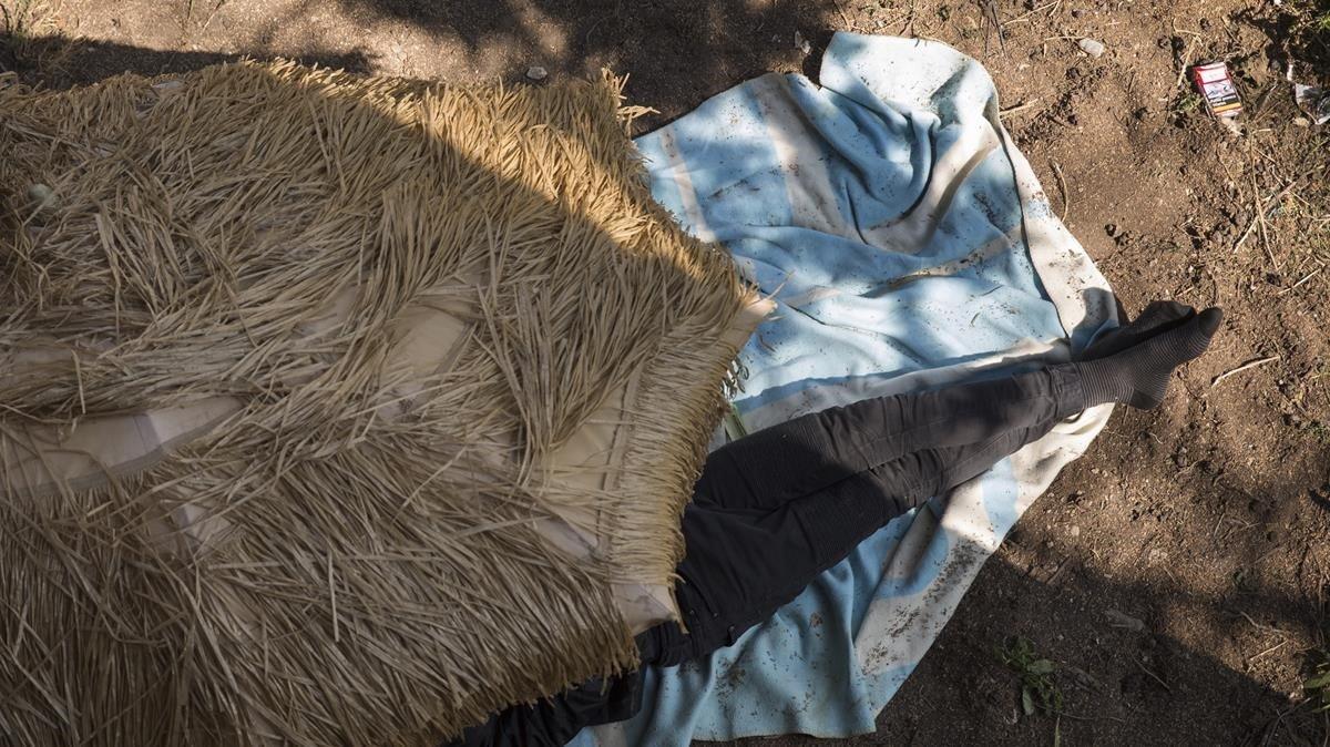 Un niño de la calle duerme bajo una sombrilla en un campamento de la montaña de Montjuïc.