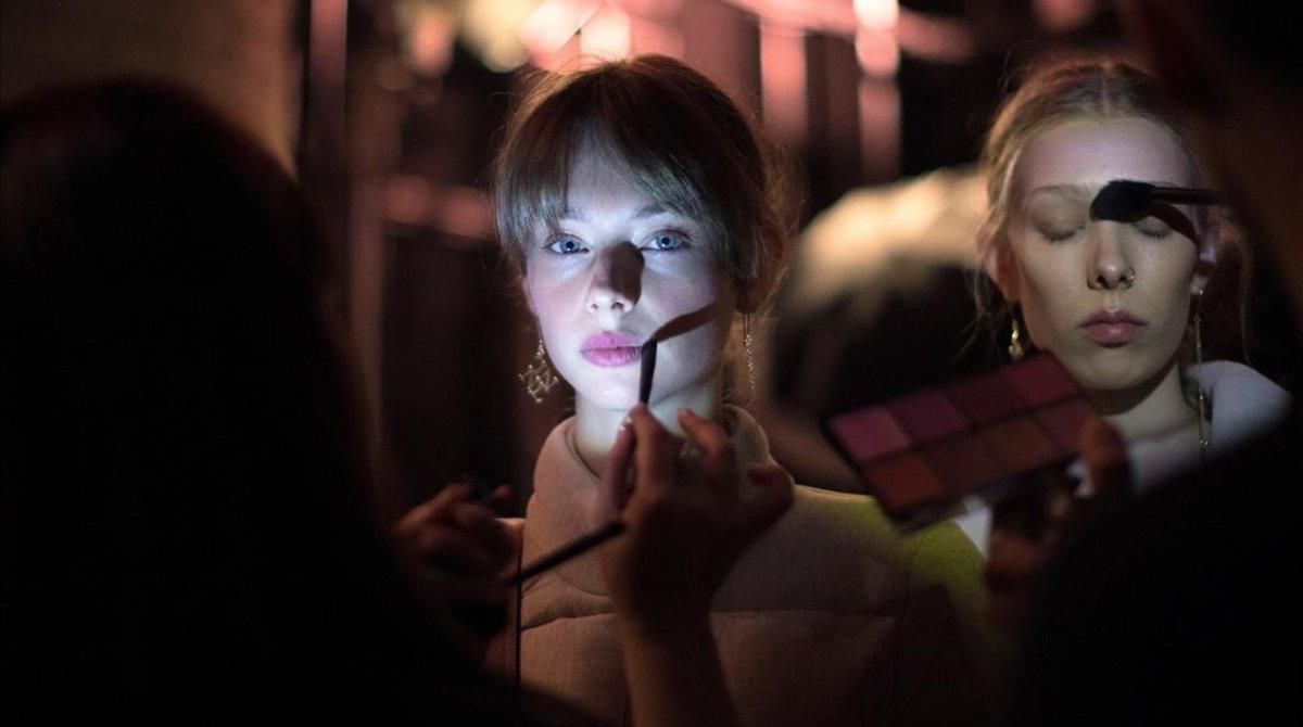 Retoques de maquillaje de una modelo antes del desfile de Naulover.