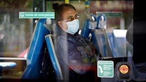 Una mujer, en el autobús, con mascarilla, este jueves.