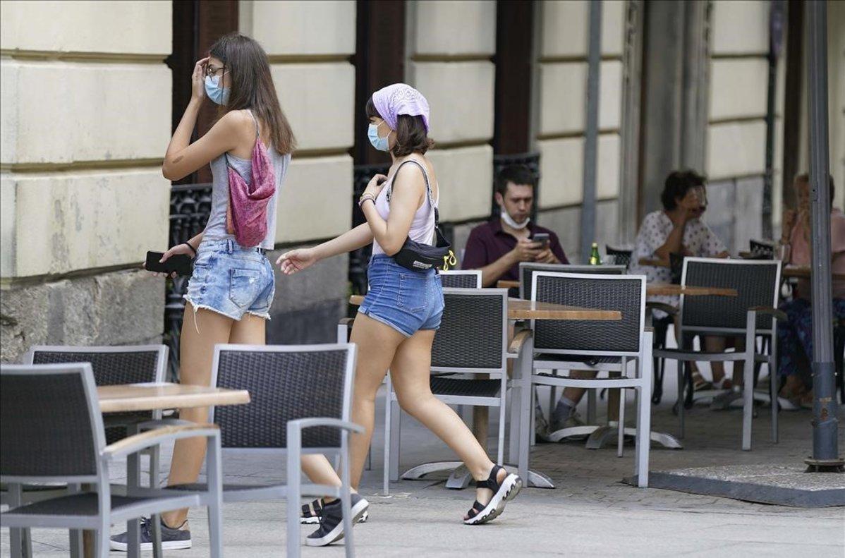 Personas con mascarilla en la calle y clientesen terrazas antes de que entre en vigor este jueves la nueva ley que obligaráa llevar la mascarilla y otras normas .