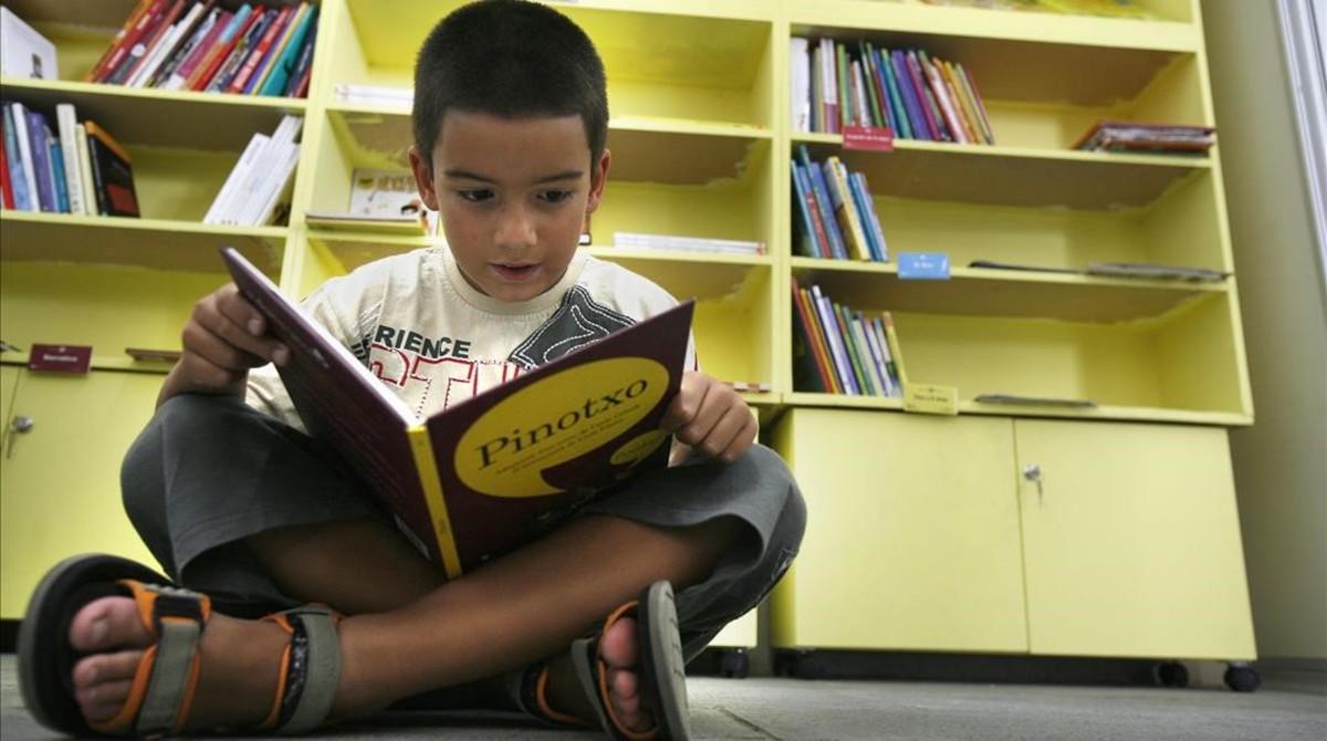 Un niño lee un cuento en una biblioteca.