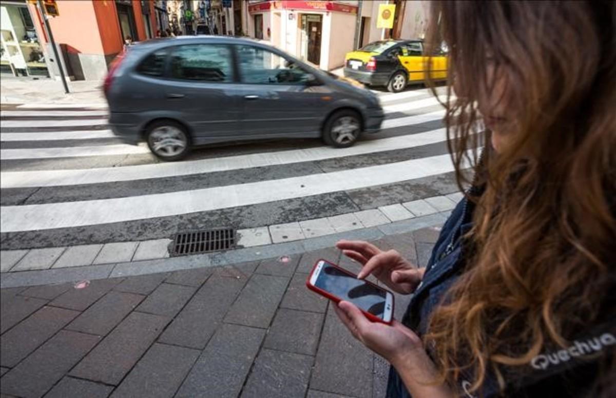 Una joven mira el móvil junto al paso de peatones de Sant Cugat con semáforo en el suelo.