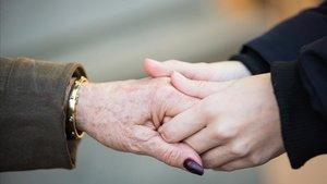 Una persona sostiene la mano de una mujer mayor.