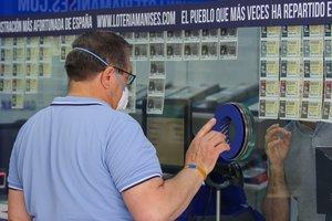 Un hombre compra lotería en una Administración en Manises durante el cuarto día desde la reapertura de su negocio dentro del proceso de desescalada instaurado por el Gobierno en el que los sorteos de EuroMillones y La Primitiva se reanudan en la semana del 18 al 24 de mayo, mientras que los de BonoLoto y El Gordo de la Primitiva lo harán en la semana del 25 al 31 de mayo. La Lotería Nacional también se puso a la venta el 18 de mayo, y el primer sorteo se celebrará el jueves 11 de junio. En Manises, Valencia, Comunidad Valencia (España), a 21 de mayo de 2020.
