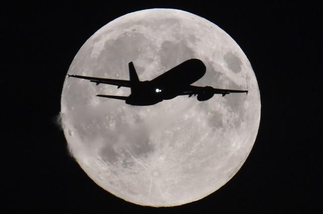 Un avión se acerca al aeropuerto de Heathrow (Londres) con la luna llena al fondo.