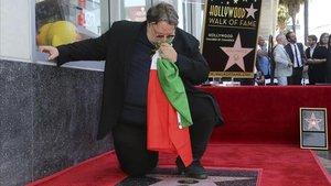 El cineasta mexicano Guillermo del Toro besa una bandera mexicana arrodillado en su recién descubierta estrella del Paseo de la Fama de Hollywood, en Los Ángeles (California, EEUU), este martes.