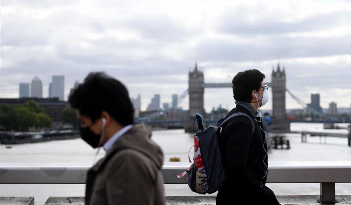 Ciudadanos con máscara pasan por el puente de Londres.