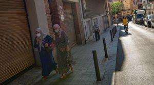 Dos vecinas de L'Hospitalet caminan por una calle casi desierta, el pasado 15 de julio.