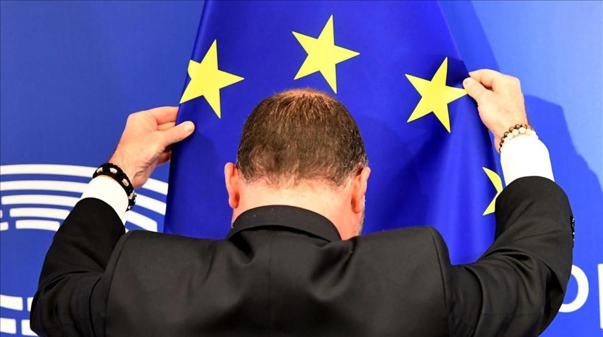Un empleado del parlamento europeo coloca la bandera de la Unión Europea antes de la conferencia de prensa.
