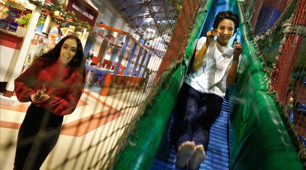 Una chica baja por uno de los toboganes del parque infantil de Sants.