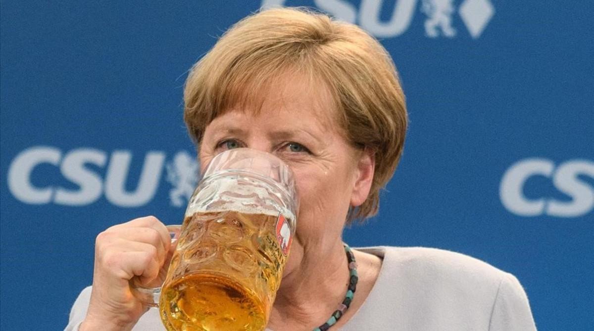 La cancillera alemana bebe una jarra de cerveza tras participar en un mitin en Múnich.