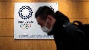 Un hombre con mascarilla pasa junto a un logo de los Juegos Olímpicos de Tokio, en la sede de la organización, en la capital japonesa.