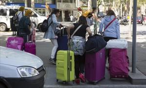 Turistas con maletas por la Gran Via de Barcelona.