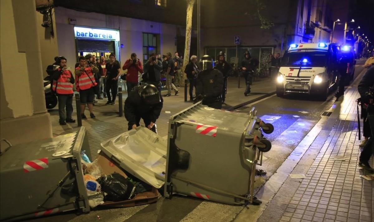 Los Mossos recogen unos contenedores volcados por los manifestantes.