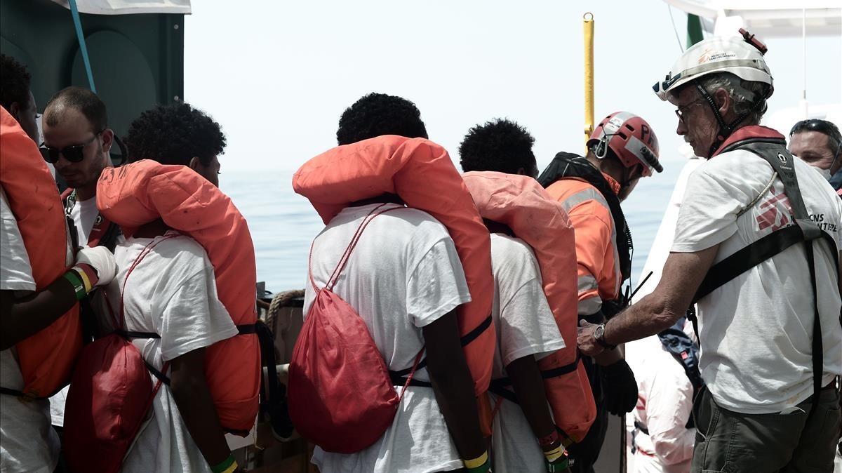 Inmigrantes a punto de subir a un guardacostas italiano.