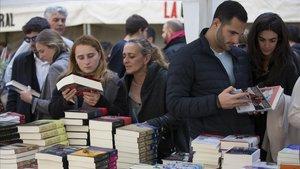 Lectores observan las últimas novedades publicadas en una parada.