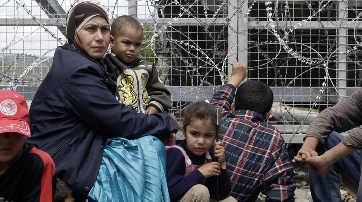 Un mujer migrante rodeada de niños, sentados junto a una valla durante una protesta por las penosas condiciones del campo de refugiados y contra el cierre del paso fronterizo de Idomeni (Grecia), este jueves.