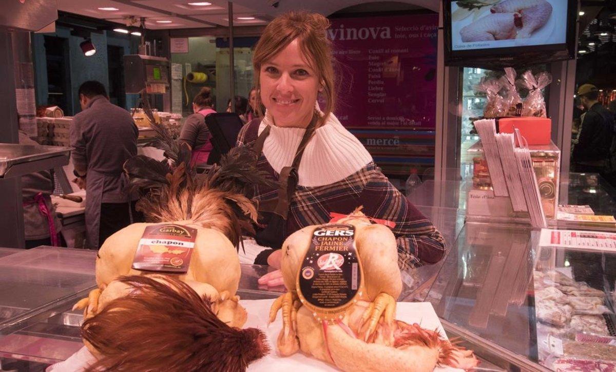 Aina Capdevila muestra el género que despacha en la parada Avinova, en el Mercat de la Concepció de Barcelona.