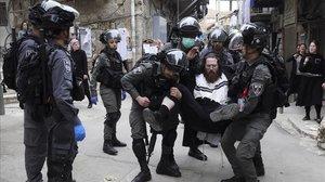 Un policía israelí detiene a un judío ultraortodoxo que protesta por las medidas de confinamiento en el barrio de Mea Shearim, en Jerusalén.