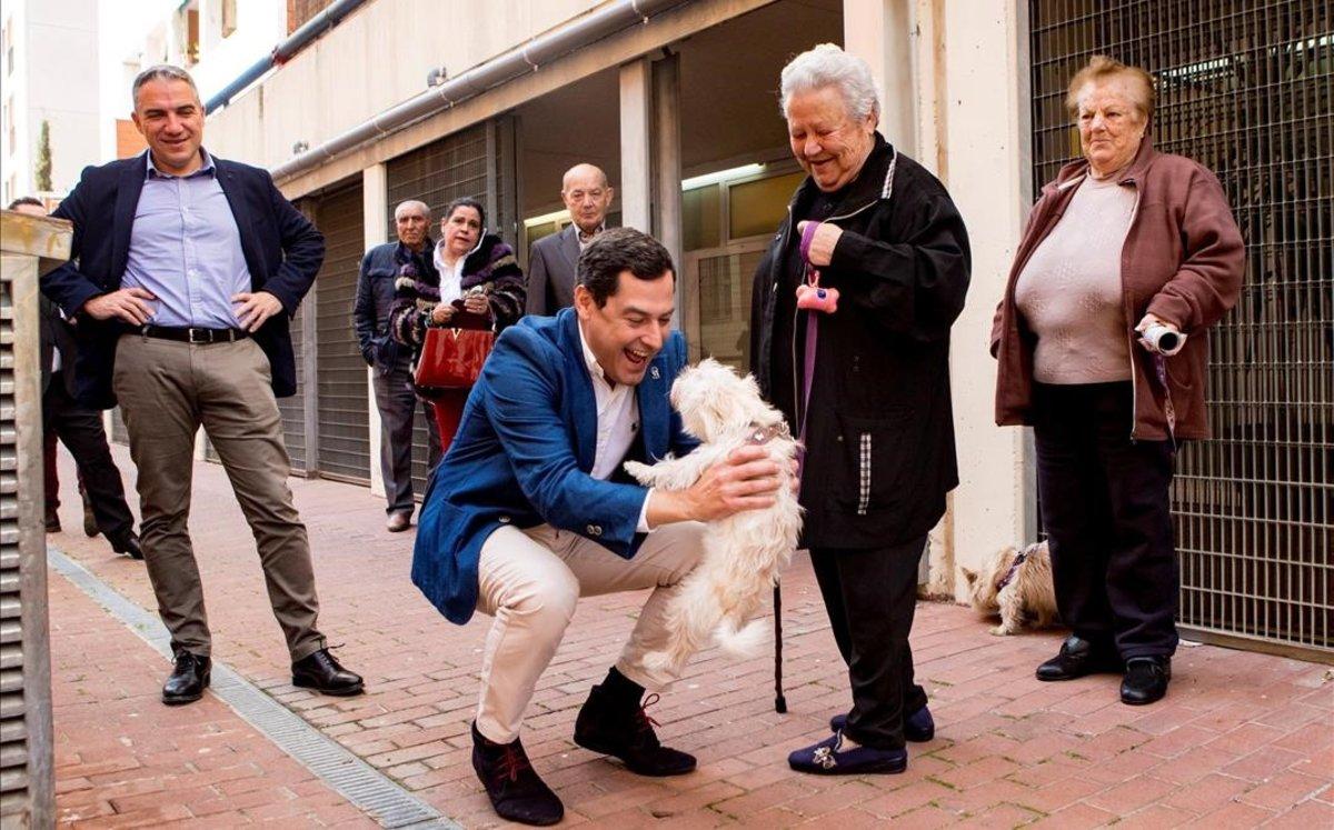 El presidente de la Junta de Andalucía, Juanma Moreno, saluda a dos vecinas del barrio de Verdum, en Barcelona.