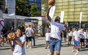 Ricky Rubio juega con los niños participantes en el acto de s fundación en la plaza Terenci Moix de El Raval