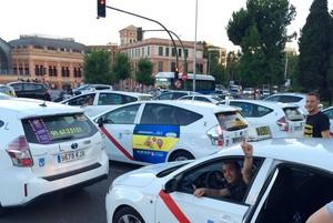 Un centenar de taxistas han participado este sábadoen la caracolada o marcha lenta de bloqueo en la Castellana Madrileña. El saludo se produce junto a la estación del AVE en Atocha, cuya glorieta de Carlos V quedó bloqueada.