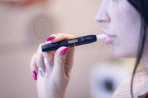 Una chica fuma con el dispositivo IQOS de Philip Morris.