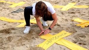 Una mujer coloca una cruz en la playa del Varador.