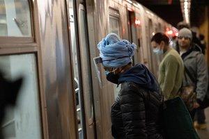 Una mujer con mascarilla y pantalla protectora en el metro de Nueva York.