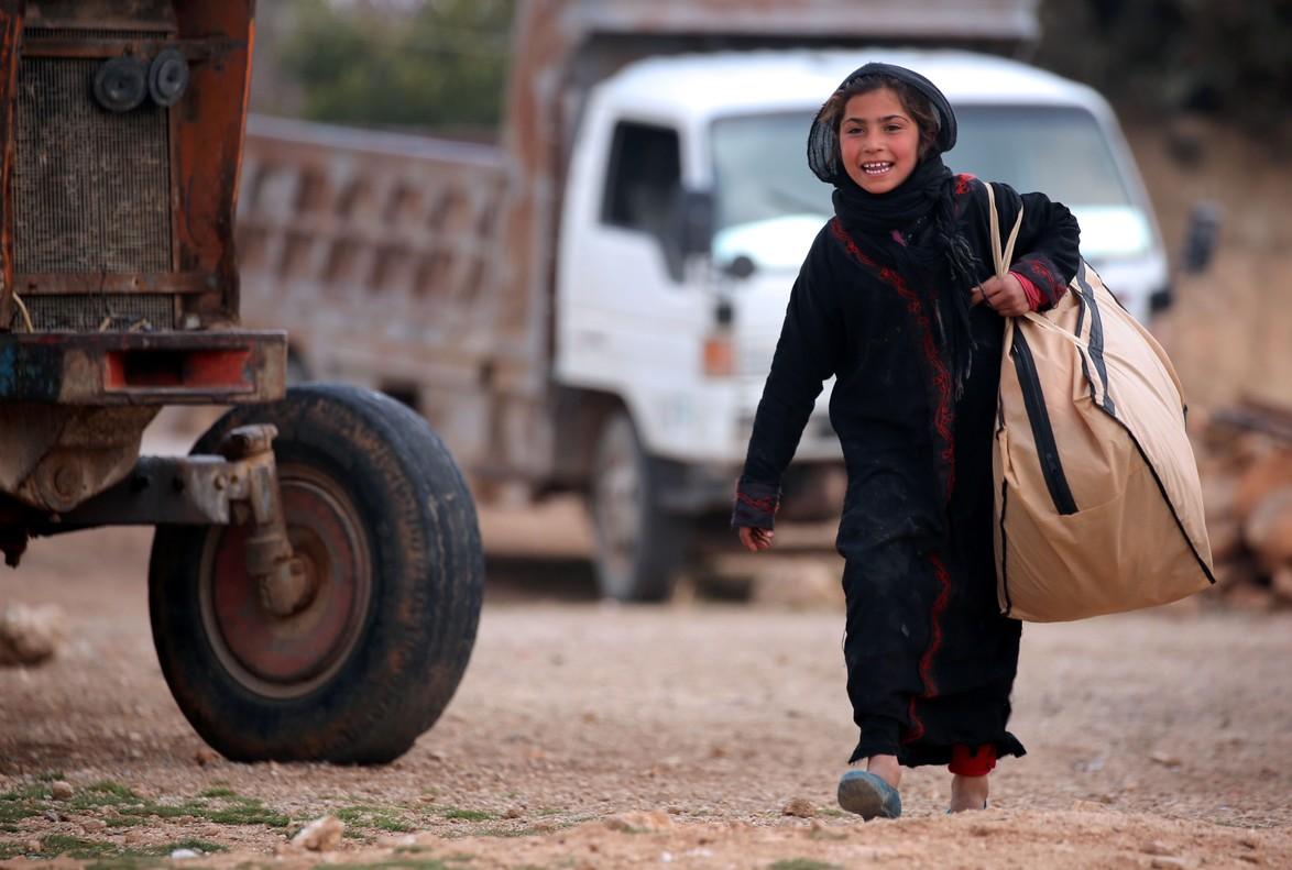 Una niña siria carga una bolsa en Jarufiya, a 18 kilómetros de Manbij.