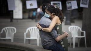 Una pareja se abraza en la plaza Reial.