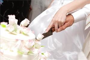 Unos novios cortan un pastel de boda.