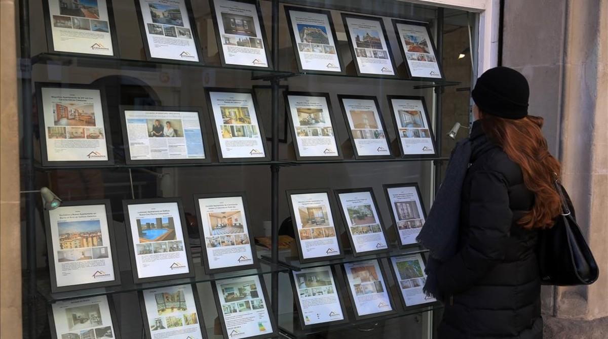 Una mujer consulta precios de pisos en una inmobiliaria.