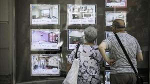 Una pareja mira pisos de alquiler en una inmobiliaria de Barcelona.