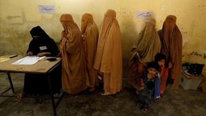 Mujeres ataviadas con burkas votan en un colegio electoral en Peshawar.