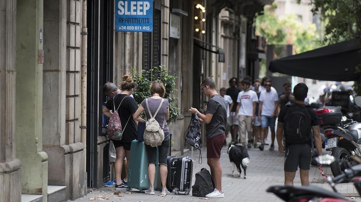 Un grupo de turistas entra en una finca de apartamentos turísticos del Eixample, el pasado agosto.