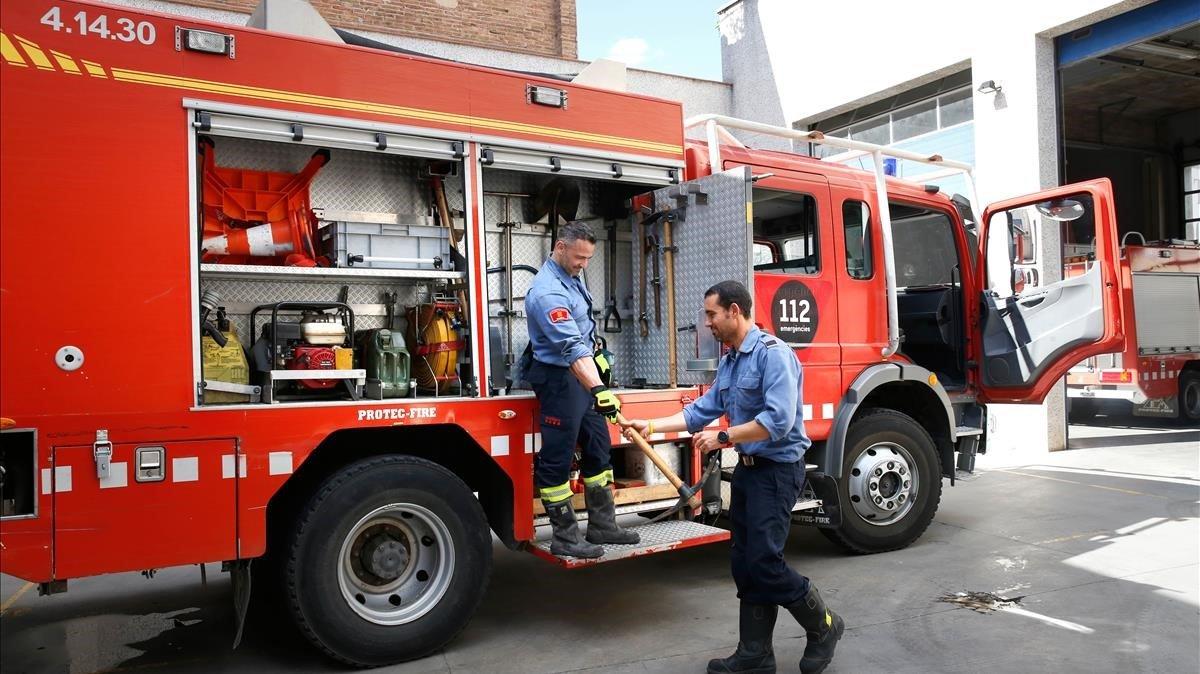 Dos bomberos revisan un camión BRP (Bomba Rural Pesada) en el parque de Sabadell.