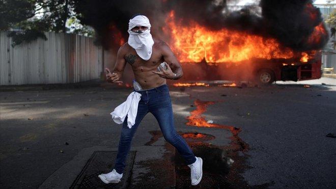 Un manifestante de la oposición hace un gesto delante de un autobús en llamas mientras sostiene una roca cerca de la Base Aérea La Carlota del Generalísimo Francisco de Miranda, en Caracas.