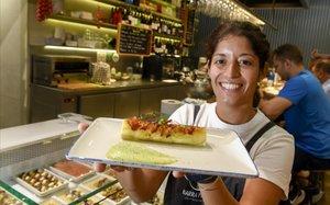 Guadalupe Reig muestra el canelón de brandada de bacalao con manzana de la barra de Perelló del mercado de El Ninot