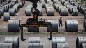 Un empleado de camina entre rollos de acero de una una planta de Changshou.