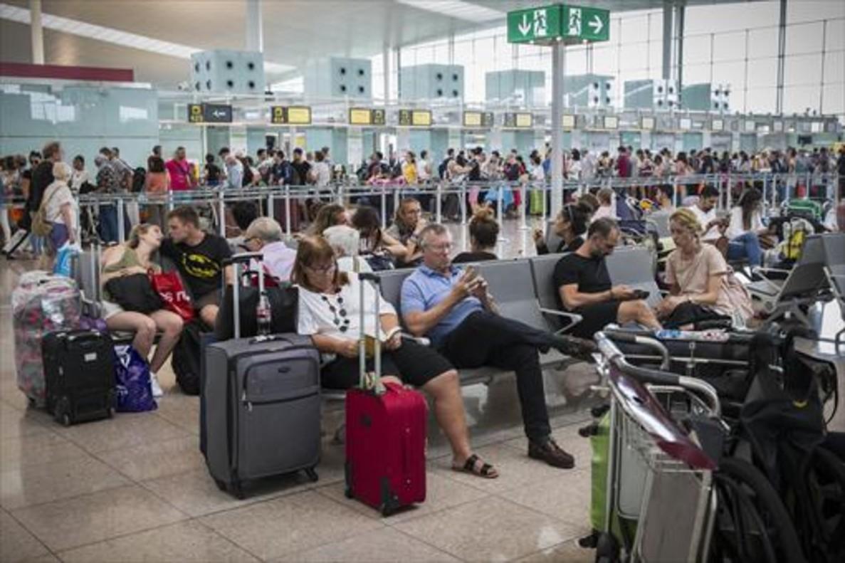 Colas frente al control de seguridad y pasajeros esperando en las instalaciones del aeropuerto de El Prat, ayer.