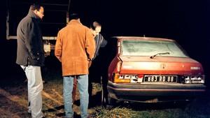 Unos vecinos inspeccionan un vehículo robado y abandonado en Naves.