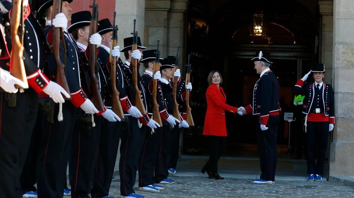 Agentes de los Mossos d'Esquadra saludan a Carme Forcadell a su llegada al Parlament.
