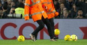 Empleados del Barça retiran los balones amarillos lanzados por un sector del público.
