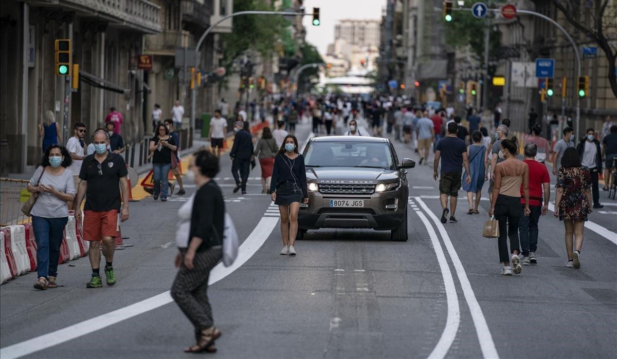 Son las 20.35 horas del 20 de mayo, el primer fin de semana que Barcelona cierra algunas calles al tráfico, cuando aparecela protagonista de la imagen, una jovenabsorta en su música, que pasea por el centro de la calzada en Via Laietana, ajena al conductor despistado que intentaabrirse paso entre los viandantes. La calle, ahora sí, es de ella.