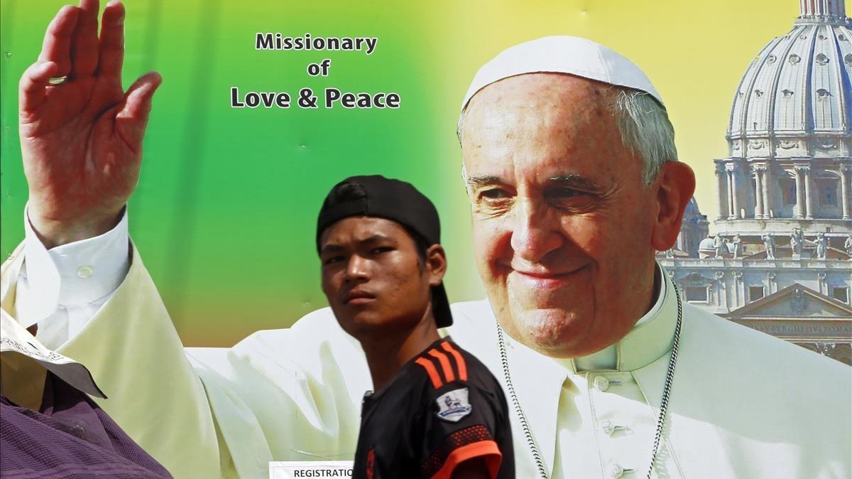 Un birmano camina junto a un poster que da la bienvenida a la visita apostólica del Papa, en Rangún, el 26 de noviembre.